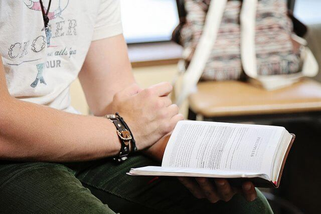 Closeup of male student reading bible